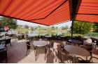 Image of folding-arm awnings fitted over seating area of lakeside restaurant.