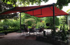 Image of syncra system fitted with  cassetted folding-arm awnings in cafe beer garden.>