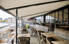 Image of pergolas fitted over seating area of a North Sea cafe.