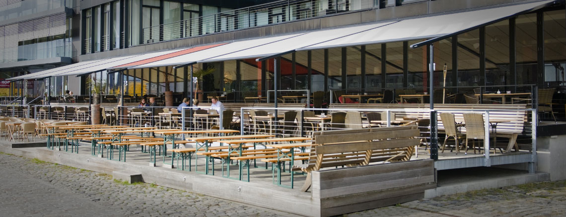 Image of coupled pergolas covering seating area outside restaurant