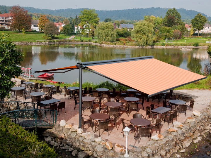 Image of syncra frame system fitted with cassetted folding-arm awnings at the seating area of a  lakeside restaurant.>